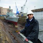 Satnam Ner, Prospect NEC member, in front of a Type 22 Royal Navy frigate being refitted in dry dock at Rosyth